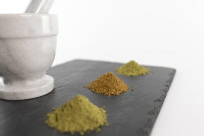 Kratom powder on tray with Mortar and Pestle